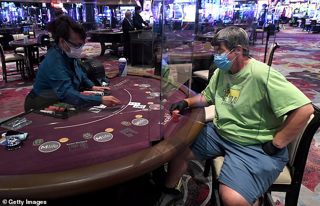 Las Vegas casinos were allowed to reopen on June 4 with masks voluntary for guests (A gambler sits at a blackjack table inside the Excalibur Hotel & Casino)