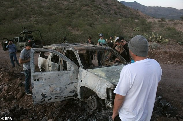 Members of the LeBarón family observe one of the vehicles where members of the Mormon family were traveling