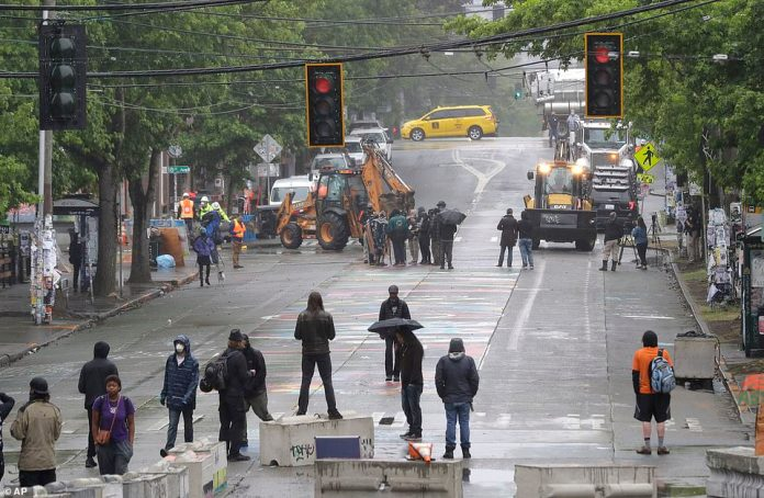 Protesters stand on barricades a block away as Seattle Department of Transportation workers remove other barricades at the intersection of 10th Ave. and Pine St., Tuesday