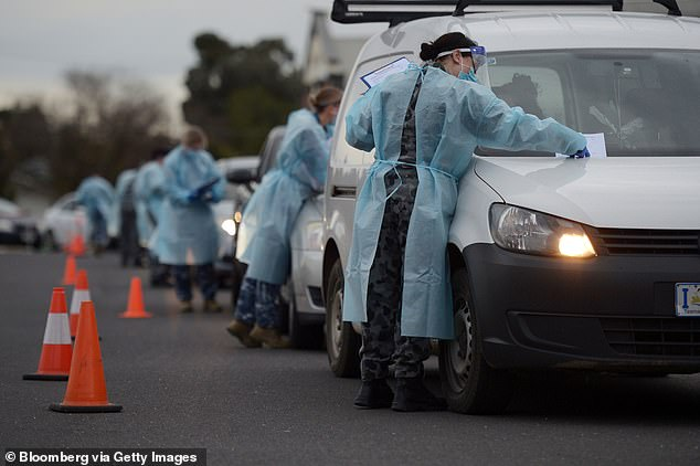 Health authorities have been scrambling to contain the outbreak with a 'testing blitz' carried out in the hotspots (pictured:Members of the Australian Defence Force do temperature checks)