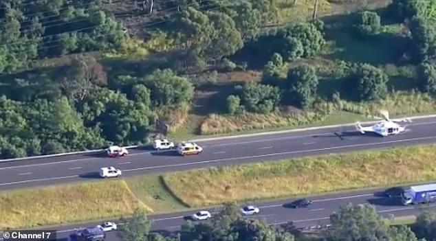 A rescue helicopter has landed on the closed highway at Mount Annan to assist the truck driver