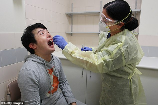 NSW recorded 14 new coronavirus cases on Tuesday. Pictured is a man being tested at St George Hospital