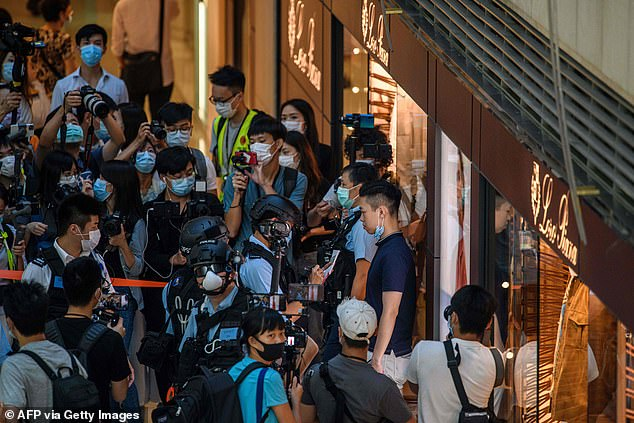 Activists say the bill will be 'the end of Hong Kong as we know it' while China insists it is necessary to restore order after months of violent clashes in the city (pictured, police search pro-democracy protesters in Hong Kong today)