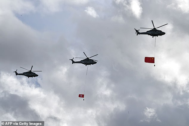 Helicopters fly the Hong Kong and China flags over Victoria Harbour as Hong Kong marks the 23rd anniversary of its handover to China