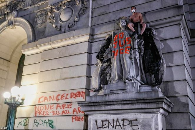 A protester climbs a statue outside Surrogate's Court near an encampment outside City Hall on Tuesday