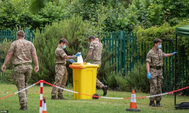 Four men in the military are pictured standing round at a mobile walk-in testing centre at Spinney Hill Park, a 34-acre green space close to the city centre