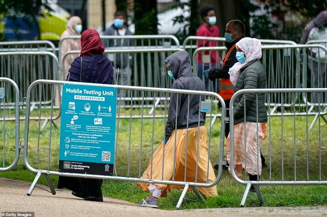 Three females wearing masks queue outside the testing centre. The city's mayor has said that pubs and restaurants may have to stay closed for two more weeks due to a surge in cases