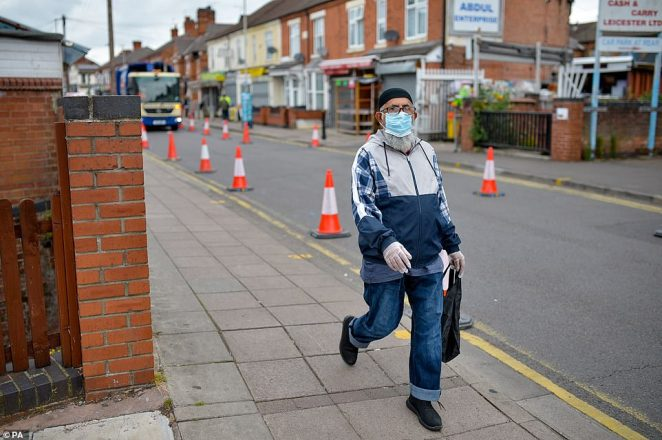 A resident walks along a street in the NorthEvington area of Leicester today amid the renewed lockdown measures