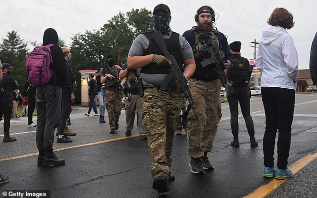 The armed men walked among protesters following the arrest of an innocent black man on June 2