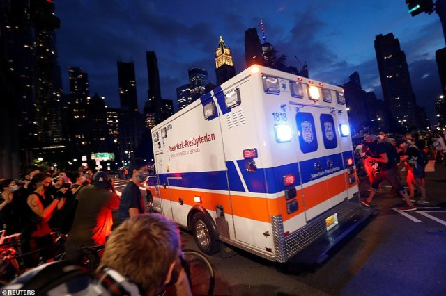 """An ambulance drives through demonstrators near of an area being called the """"City Hall Autonomous Zone"""""""