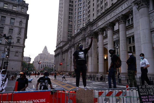 Earlier in the morning, protesters stood atop a barricade with 'abolish police' signs taped to it