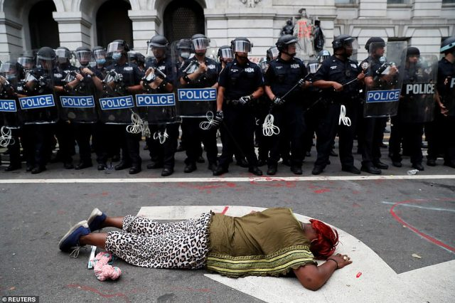 A different protester lay face down in the street. It's unclear if they were one of the three people later arrested