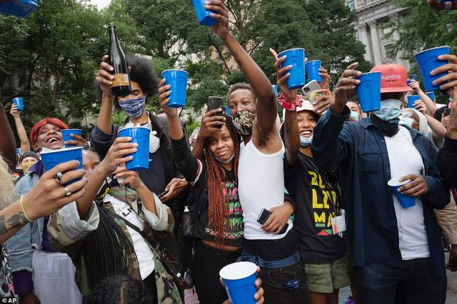 Protesters toasted with prosecco and champagne on Wednesday morning after the NYPD had $1billion stripped from their budget