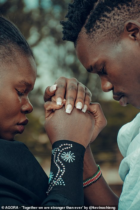 Pictured: A black woman and man clasp hands and bow their heads in a photograph titled 'Together we are stronger together'