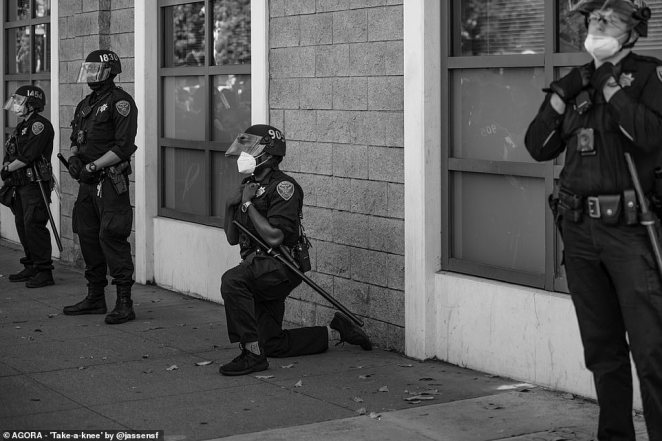 Pictured: A police officer in the U.S. takes a knee, an act that has become to be a sign of solidarity with the black community and protest against police brutality