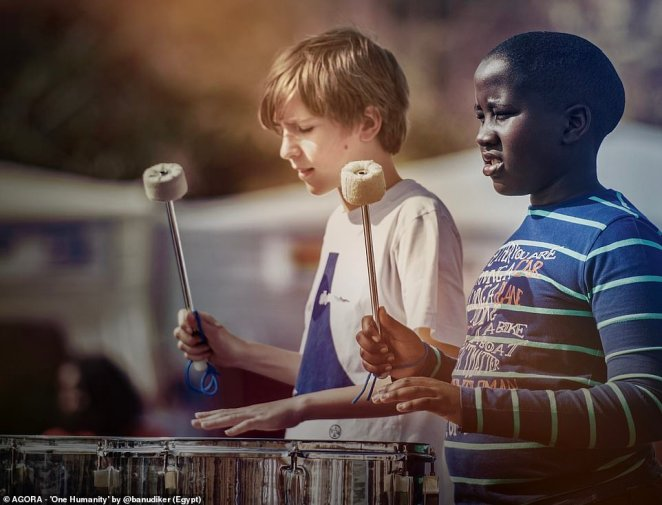 Pictured: Two boys - one white and one black - play the drums together