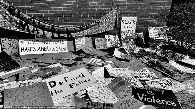 Signs made by anti-racism protesters, with messages including 'Black Lives Matter', 'Love not hate makes America great' and 'Defund the police' lie on the ground and are propped against a wall in the U.S.