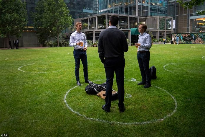 Drinkers stand in marked rings on the grass to maintain their social distance outside a bar in Canary Wharf, East London, yesterday
