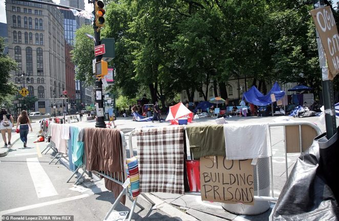 Demonstrations calling for an end to police brutality and systemic racism show no signs of abating in the Big Apple where protesters have set up camp. Clothes and sheets are pictured hanging over the railings in the area Thursday