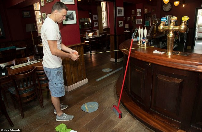 Sylvester Kowalczk pictured measuring 2m to put social distancing stickers on the floor at the Ship and Whale pub in Rotherhithe, south London