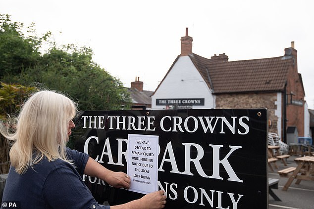 Some pubs in areas such as Leicestershire have chosen not to reopen tomorrow. Above, Landlady Carole Burton at The Three Crowns in Barrow upon Soar, in northern Leicestershire, puts up a sign saying they will not be opening due to the local lockdown