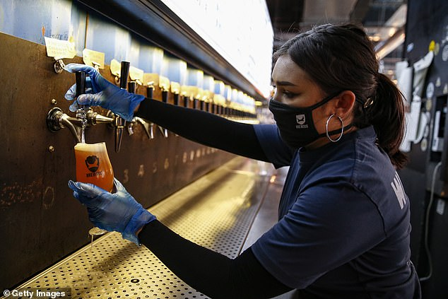 Pub staff will likely have to wear personal protective equipment (PPE) when pubs reopen to protect from the potential spread of coronavirus. Pictured: Staff at BrewDog Tower Hill prepare to reopen tomorrow with social distancing measures in place