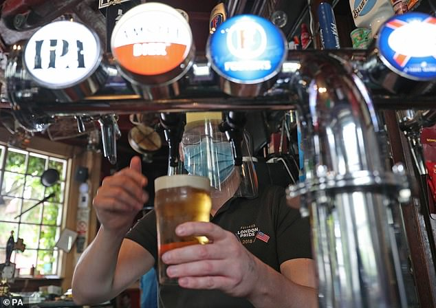 Above, Barman Michael Fitzsimons wears PPE while pouring a pint during final preparations at The Faltering Fullback pub in North London
