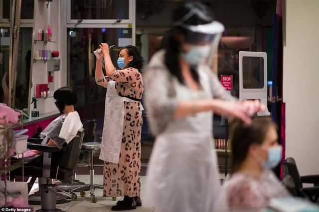 A stylist adjusts her protective face shield as customers visit Tusk Hair stylists in Camden