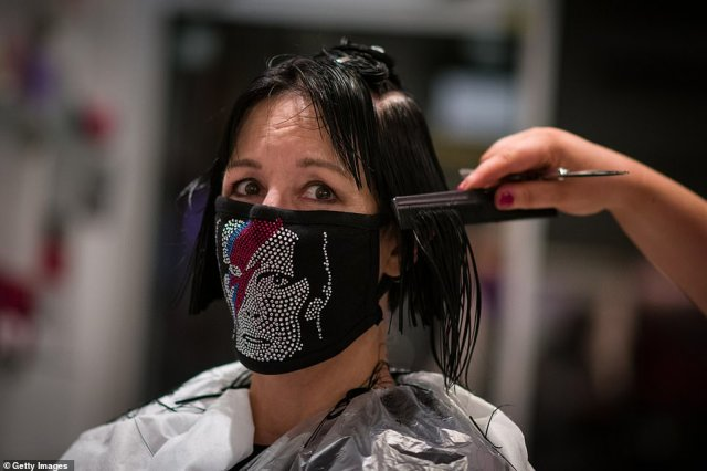 A customer wears a face mask emblazoned with a David Bowie image at a north London salon