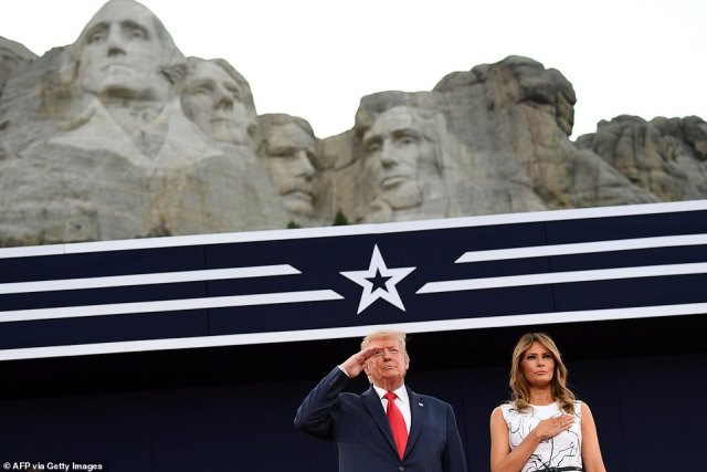 Mount Rushmore can be seen above President Trump (left) and First lady Melania Trump (right) as the pair salute the flag and pay their respects during the National Anthem