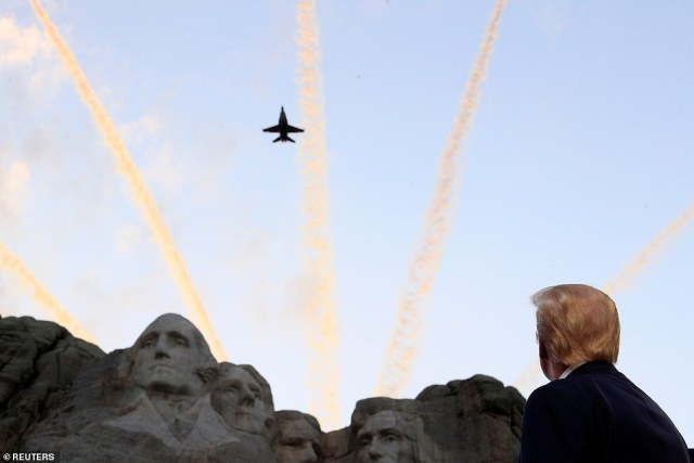President Trump is seen taking in a flyover at Mount Rushmore Friday night before he gave a fiery campaign speech