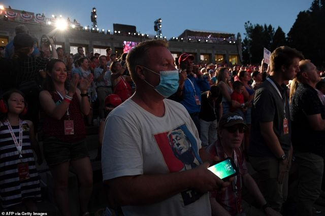 A Trump supporter protects himself from coronavirus by wearing a mask in the stands. Gov. Kristi Noem did not enforce social distancing at the Friday night speech and said masks were optional