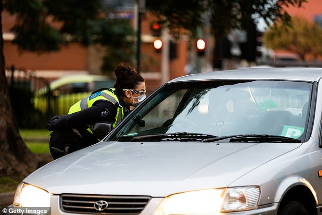 A police officer speaks to a driver entering the housing commission flats in the suburb of Flemington
