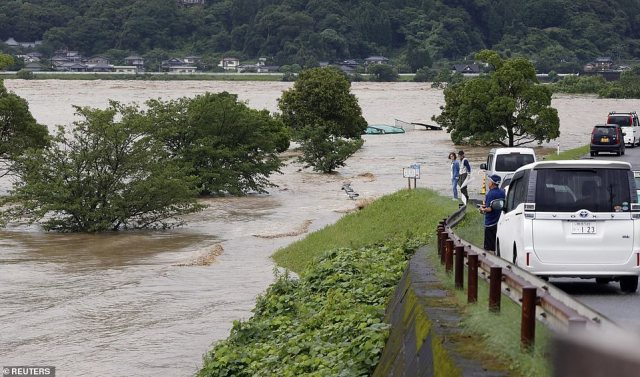 A massive landslide destroyed several houses with rescuers searching for missing people through half-buried windows. Pictured: rising water caused by a heavy rain is seen along Kuma river in Yatsushiro