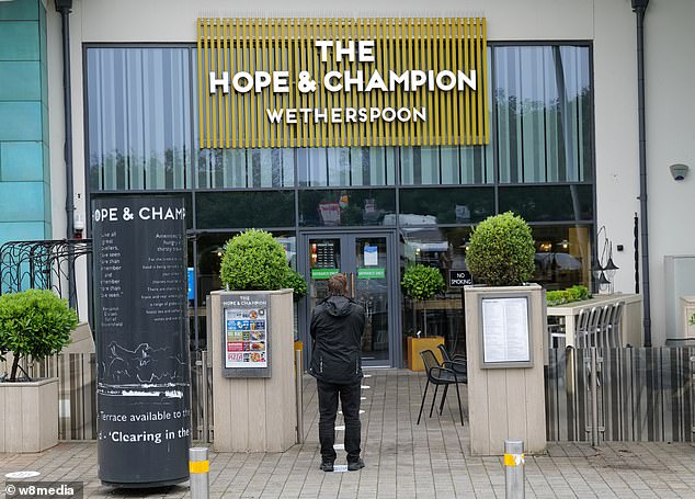 England is braced for 'pub-ageddon' as bars and restaurants reopen on Super Saturday but fears of 6am mayhem were calmed with most not set to start serving until after 8am. Pictured: A Wetherspoons in Beaconsfield this morning