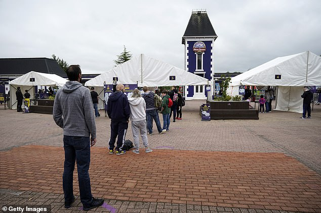 Thrillseekers queue outside the front of Alton Towers in Alton, near Stoke, as they wait to go on rollercoasters for the first time in months