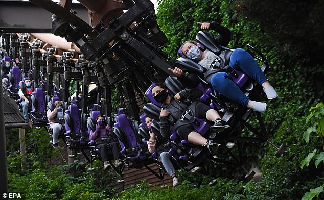 People enjoy a ride at the Chessington World of Adventures in Chessington in Surrey as the park reopened following months closed