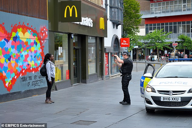 Residents of Leicester were ordered to remain at home as hoards of merry drinkers in other parts of England flocked to pubs on Super Saturday. Pictured: Police inLeicester city centre today
