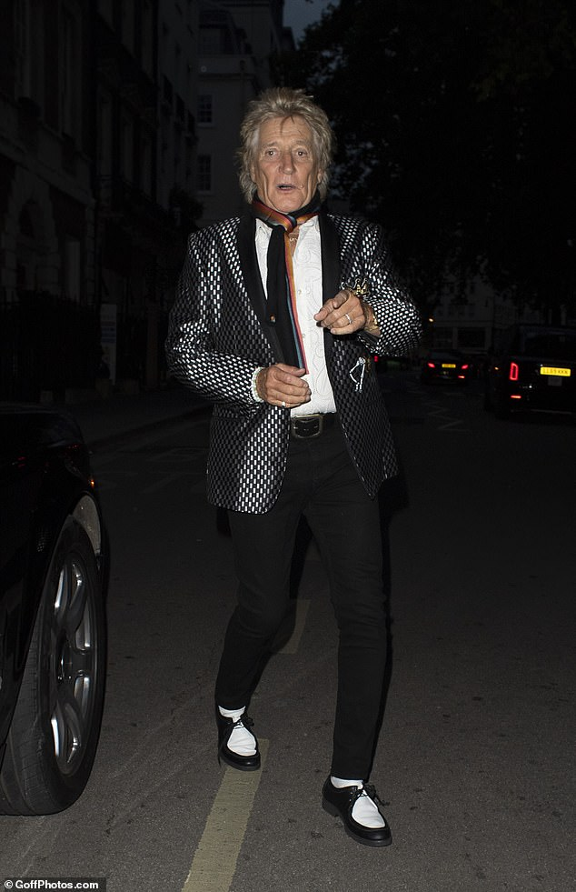 Fashionista: The rocker, 75, cut a stylish figure in a monochrome ensemble before adding a pop of colour with a striped scarf wrapped loosely round his neck