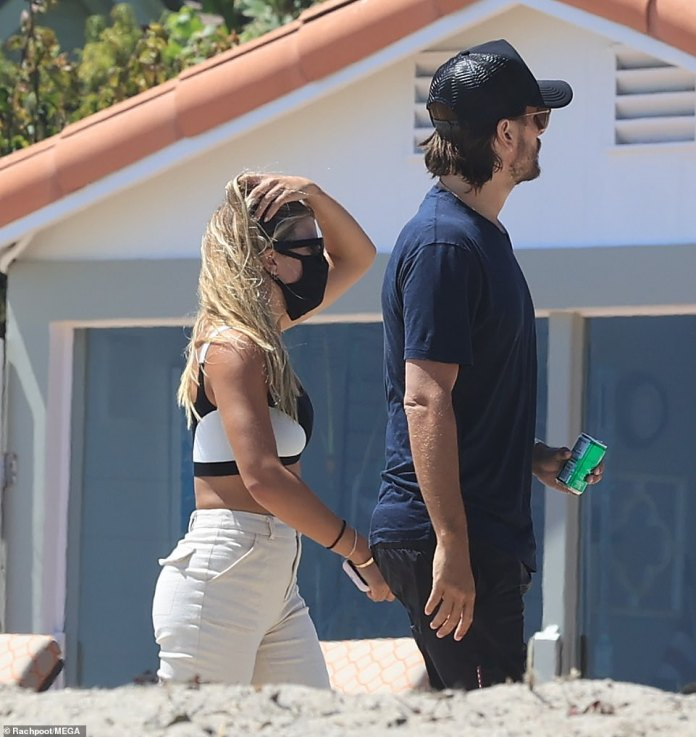 Strolling: Sofia ran her fingers through her hair as she and Scott strolled the property by the sea