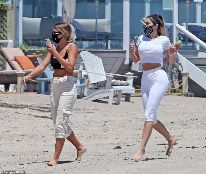Girl time: Sofia and her female companion walked along the shore together as she took a phone call