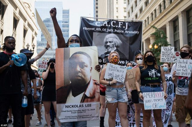 "Hundreds of people held images of gun violence victims and Black Lives Matter protest signs like ""Amerikka was never free or great' during a demonstration in Chicago, Illinois"