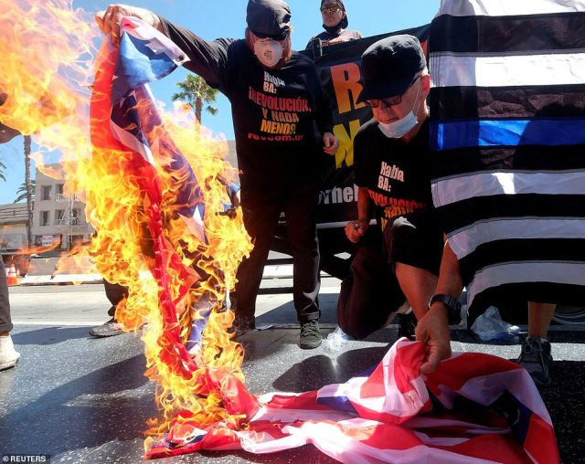 Gregory 'Joey' Johnson (right) burns a U.S. flag near Donald Trump's star on the Hollywood Walk of Fame during an anti-Trump rally in in Los Angeles, California . Johnson's burning of an American flag in Texas in 1984 led to a U.S. Supreme Court ruling upholding the act as free speech