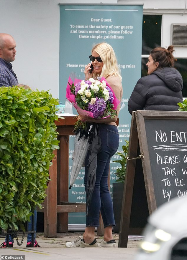 Celebrations?  Holly was also seen holding a pretty bouquet of flowers outside the pub
