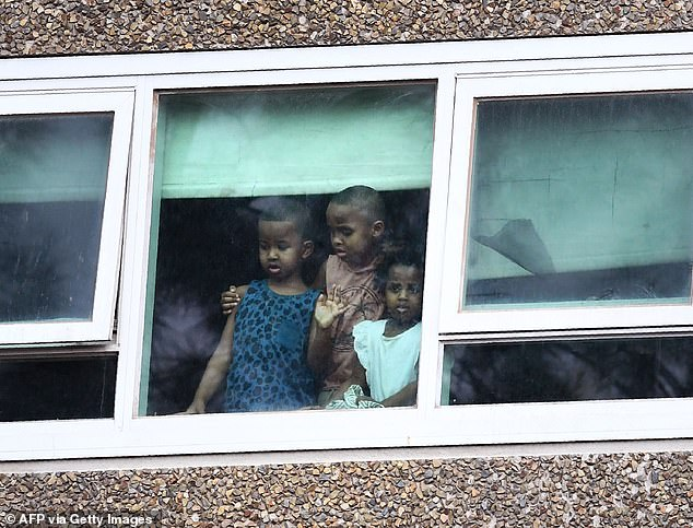 Residents look from a window at one of nine public housing estates locked down due a spike in COVID-19 coronavirus numbers in Melbourne