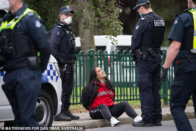 The young mum sits on the ground and talks to police after she was arrested on Tuesday outside the towers in Flemington