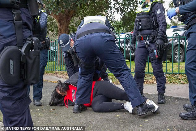 Police grapple with the young mum in Flemington on Tuesday