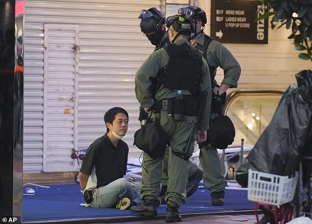 The DFAT warning said Chinese authorities had detained foreigners for 'endangering national security'. Pictured: Democratic Party politician Hui Chi-fung is detained by riot police during a protest in Causeway Bay in Hong Kong on June 12