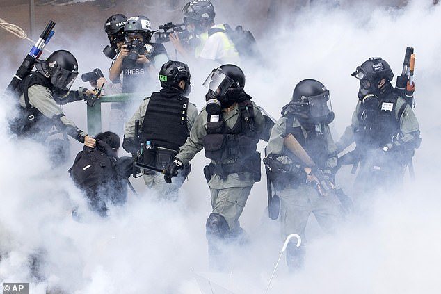 Police rush through smoke to detain protesters during a demonstration at the Hong Kong Polytechnic University in November 2019