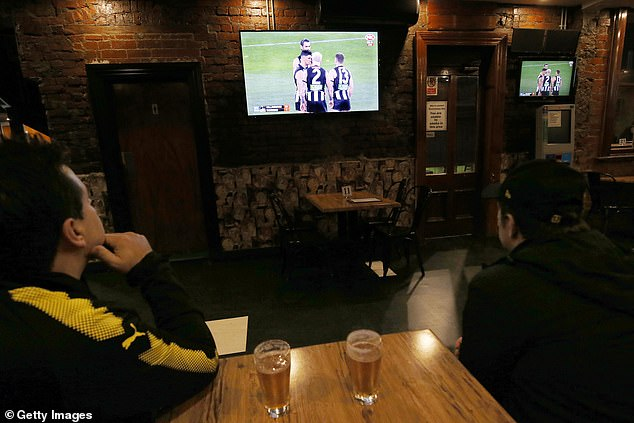 Sit-down restaurants, cafes, bars and eateries will once again have to close once again. Pictured: AFL fans watch a game at a Richmond bar after restrictions were eased in June